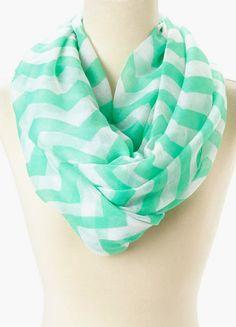 La bufanda tiene rayas.  Los colores de rayas son blanco y turquesa.  Es una bufanda infinito.