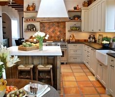 The owner wanted to feel like they were returning to France when they visited their Santa Fe home. We selected greige cabinets, soapstone counters, brick accents and saltillo flooring to create a French country feel. The counter is topped with Carrera Mist marble. An old Indian door was installed on a rolling track for the pantry door.