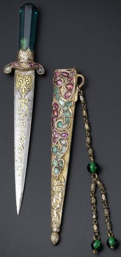 Ottoman dagger with the tughra of HIH Princess 'Adile Sultan (1825-1898), 19th c, green glass hilt, quillons set with rubies and emeralds, gold damascened inscribed blade, gilt scabbard set with rubies and emeralds, chased to depict a trailing vine, verso with a trailing vine and scale design chape, suspension loop, faceted sectioned chain and green glass beads, 11.7 cm. long, based on a 17th c. prototype, an emerald-hilted example in the collection of Topkapi Saray, Istanbul.