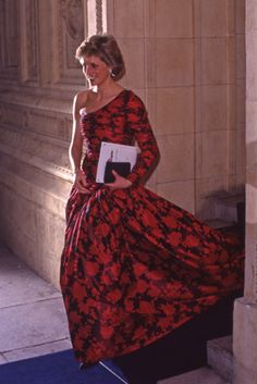 Princess Diana dressed in a red and black one shouldered gown.