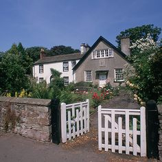 White picket gates leading to rose-lined drive and country garden