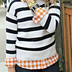 Plaid shirt under a stripped sweater.