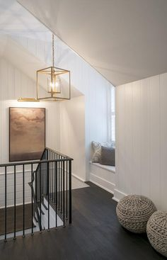 Second floor landing boasts vertical shiplap walls fitted with a built-in window seat alongside a pair of gray knitted poufs illuminated by a gold cage lantern.
