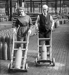 "Chilwell munitions factory, Nottinghamshire, transport shells across the factory floor, c. Each is pushing a sack barrow. The original caption reads: """"Eighteen and eighty doing their bit"". World War One, Second World, First World, Historical Photos, Historical Clothing, Ww1 Soldiers, German Submarines, Rosie The Riveter, Working People"