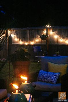 String lights on the fence  pretty torches to light the backyard at night