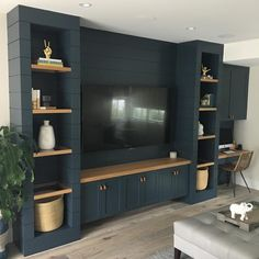 Beautiful dark blue custom entertainment center, with white oak glass-framed shelves and desk surfaces. 😍😍 @brookewagnerdesign…