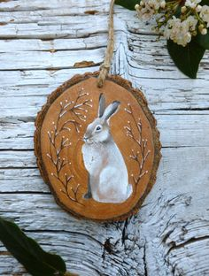 *Artist Made*  Original, hand painted illustration of a pretty winter rabbit, with lucky foot symbol on reverse  Dimensions Height: 9.9cm Width: 8.2cm Depth: 0.5cm  This listing is for the exact wooden ornament shown. It is a unique item and would make a very thoughtful gift. Please see the front and back view of the ornament. This double sided design allows for the ornament to spin and hang gracefully, this way all angles of the ornament can be appreciated. This design channels the…