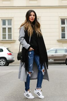 Consuelo Paloma pulls of the sporty look to perfection, by pairing her sneakers with her grey overcoat. Her ripped jeans and oversized scarf add a casual element to the outfit  Coat and Sweater: Shein, Jeans: Zara, Shoes: Adidas, Scarf: H&M.