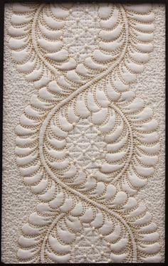 Intertwining quilted feathers with scribble stitch background