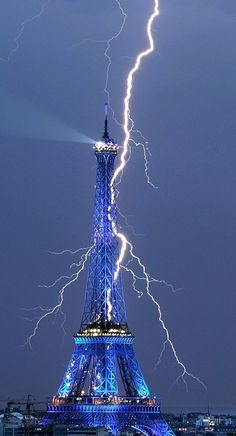 Eiffel tower lights up blue as lightning strikes it...