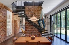 Metallic spiral staircase and exposed brick walls steal the show on the lower level living room