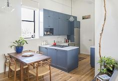Claire and Mike loved everything about their co-op in a converted Brooklyn industrial building, except for the kitchen. In appearance it was rather inoffensive — not nearly as terrible as some of the 'before' kitchens we've seen on this site — but in storage ad counter space it was seriously lacking. Also, with its standard-height cabinets, the kitchen looked awkward and squatty in such a tall space.