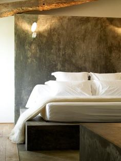 Gorgeous balance of crisp white/cream wall and bed linen, with the hard textured grunge. photo Gabriel Jean-Pierre