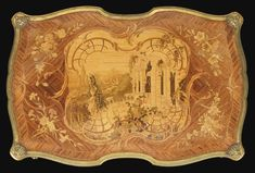 A GILT BRONZE MOUNTED marquetry-TABLE SIGNED F. LINKE, IN LOUIS XV STYLE the scalloped shaped plate decorated with ruins and landscape in a frame with scrolls and bouquets of flowers, surrounded by a mold decorated with lion masks at the corners; the waist opening with two drawers, decorated on the sides of grenades in cartridges, based on arched summed amounts of shells and plants, and ending with claw feet