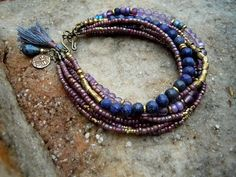 A seven strand bracelet in muted colors of lavender to purple and deep blue with golden accents.I used lapis lazuli beads, ( vary from smooth to faceted ) light lilac color amethyst, small african brass trade-beads and various size czech beads in lavender to purple hues. A brass dragonfly charm, a teardrop shape lapis bead …