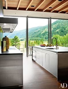 An Aspen kitchen with bead-blasted stainless steel cabinetry and floor to ceiling views| archdigest.com