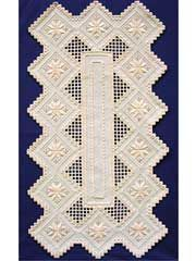 """The star table runner pattern uses the following stitches: kloster blocks, satin stitch, bar weave, double cable, single cable, blanket stitch, double running stitch, cross-stitch and eyelets. Finished size: 15"""" x 28""""."""