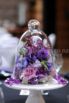 Purple lisianthus, stock, anemones, singapore orchids and Delilah roses inside a glass cloche sitting on a cake stand. Flower Arrangement Designs, Flower Designs, Floral Arrangements, Glass Bell Jar, Glass Domes, Bell Jars, Deco Floral, Floral Design, Cloche Decor