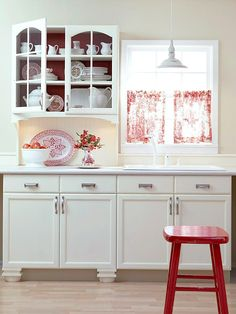 Swedish Country Classic; white paint and chrome hardware refresh the cabinet's exteriors.  an arched fascia on upper cabinet and curved side brachets btwn the fascia and the countertop create the illusion of a formal hutch.  a beaded board backsplash enhances the look.  removing the valance above the sink then adding simple red and white toile curtains, creates classic Swedish country style. bhg.