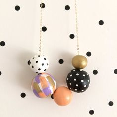 Add a unique touch to your outfit with this one of a kind statement necklace! It features hand painted wooden beads in peach, lavender, black,