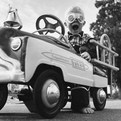 young boy playing in his fire truck