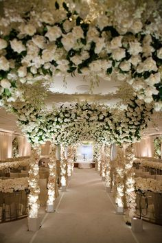 The couple's indoor wedding ceremony was inspired by a European garden. Arches adorned with greenery and white tea roses ran the length of the aisle, and gates surrounding ceremony seating were also embellished with snowy florals. #weddingceremony #decor Photography: Jose Villa Photography. Read More: http://www.insideweddings.com/weddings/destination-beverly-hills-wedding-with-celebrity-chef-performers/467/