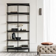 Modular bookcase with frame in titanium (GFM11), white (GFM71), black (GFM73) or graphite (GFM69) embossed lacquered steel. Shelves in Canaletto walnut (NC) or burned oak (RB) or embossed white (GF71) or graphite (GF69) painted wood. Brass details. For the freestanding use are recommended at least two modules.