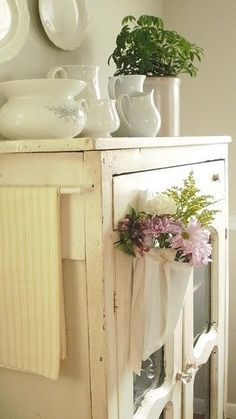 pretty white china, white cupboard and flowers...