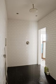 Black and white shower room featuring subway tile shower surround as well as rain shower head over black shower floor. Bathroom Spa, Bathroom Renos, Laundry In Bathroom, Modern Bathroom, Bathroom Lighting, Bathroom Ideas, Dream Bathrooms, Beautiful Bathrooms, Orange Bathrooms