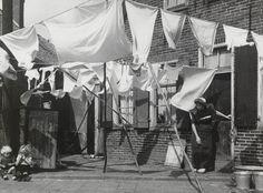 Waslijnen met wasgoed te Spakenburg. Rechts een vrouw in streekdracht. Ze is gekleed in daagse dracht en is in de rouw. 1948 #Utrecht #Spakenburg