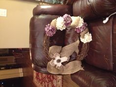 Wooden wreath with burlap ribbon, hydrangeas, cross from hobby lobby. floral wire and hot glue to attach it all on the wreath!!