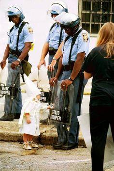 1 niño del KKK tocando el escudo de un policía negro