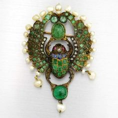 An Egyptian Revival gem set scarab brooch, circa 1900. Emeralds, sapphires, pearls, rubies and rose-cut diamonds in yellow gold, partially silver-topped.