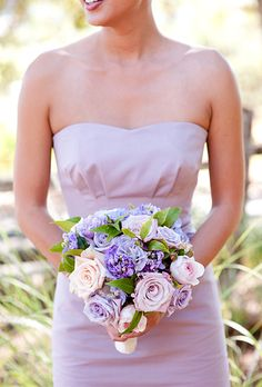 Brides.com: . Bridesmaid Bouquet of Roses, Lisianthus, Sweet Peas, and Scabiosa. A round bouquet of formal rose blooms can be made romantic with a pastel color palette of pink, purple, and green.  See more photos from this California vineyard wedding.