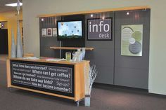 """info center. we could get a bookshelf and paint the back maybe put some wording on it like here and use the shelves for storage (business cards, brochures, flyers, etc.) and paint that wall behind the table a different color than the rest of the lobby so that there was a """"designated"""" area."""