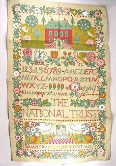 Pat Albeck linen tea towel. Bright, colorful sampler scene.