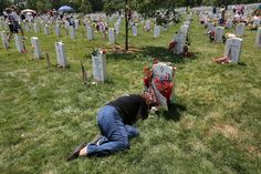 Karen Clarkson lies over her slain son's grave at the National Cemetery on Memorial Day. Her son, Sgt. Joel Clarkson, was serving as an Army Ranger team leader in Afghanistan when he was shot and killed in March 2010.