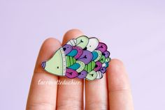 Hedgehog brooch made from 2mm thick plexiglass (hand sawed). Hand illustrated and varnished to protect color and ink. It is measures approximately 4 cm x 3 cm (1.5 x 1.2 inches). It comes in a gift...