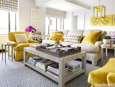 Yellow and gray living room features an English roll arm sofa adorned with yellow velvet pillows.