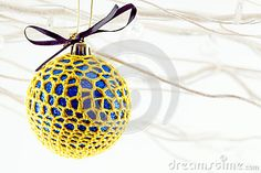 A close up  of  a blue sparkly bauble covered with yellow crotchet