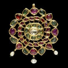 A gem-set gold Pendant  India, 19th Century in the form of a rosette, set with rubies and emeralds in gold around a central diamond in an open framework, three pearl beads suspended below, gold suspension loop above, the reverse plain gold