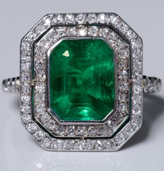 Art Deco platinum ring with octagonal bezel adorned in the center with a Colombian emerald bezel set in a double circle of small brilliant-cut diamonds and mounted crimped closed platinum . The emerald weighing 2.90 carats. It is accompanied by a certificate from Paris gemological laboratory certifying the Colombian and the absence of resin.