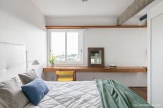 Bancada de madeira se estende por todo o quarto e adquire funções diferentes como penteadeira e home office.