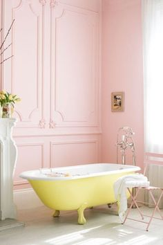 a fun sunny yellow clawfoot bathtub in a pink bathroom