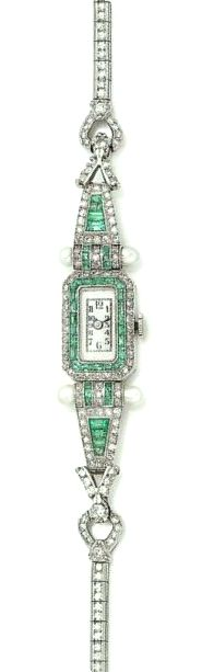 An emerald and diamond wristwatch, circa 1925 The rectangular dial with Arabic numerals within a surround of calibré-cut emeralds and single-cut diamonds with cultured pearl highlights, tapering to a bracelet set with a single row of single-cut diamonds, diamonds approx. 3.50cts total, French assay marks, length 19.0cm, fitted case