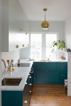 an eye-catchy teal and white kitchen with brass touches looks chic and very inviting