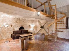 Petit salon sous la mezzanine. Escalier hélicoïdale ajouré en bois. Mur en pierres apparentes, carrelage en terre cuite