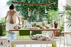 View of casually laid wooden dining table with plants and green accessories. Customised wooden NORNAS bench with botanical print cushions.