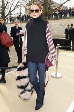 Olivia Palermo keeping cozy in a striped blouse underneath a turtleneck sleeveless knit, and flared jeans