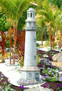 Photo of lighthouse ornament surrounded by tropical plants.